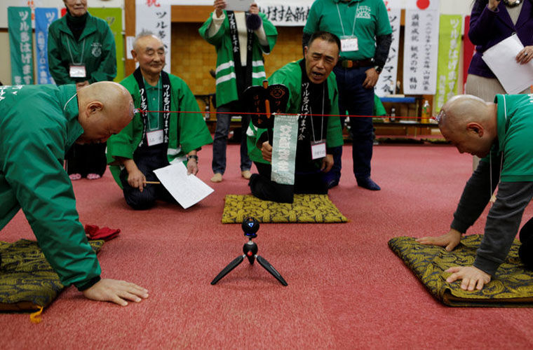 Members of the Bald Men Club, take part in a unique game of tug-of-war by attaching suction pads onto their heads, at a hot spring facility in Tsuruta town by STAFF.