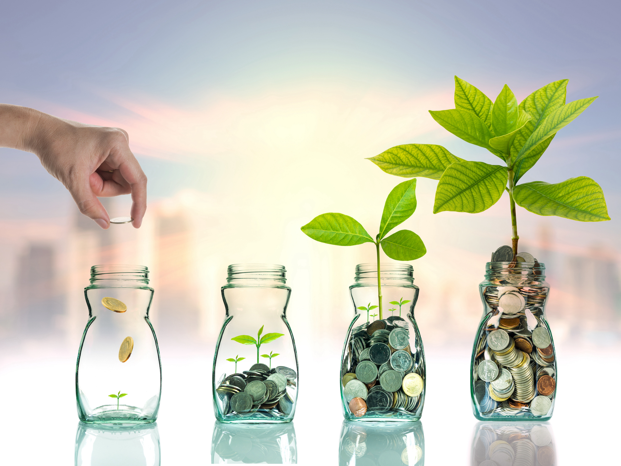 Hand,Putting,Mix,Coins,And,Seed,In,Clear,Bottle,On by Copyright (c) 2015 TZIDO SUN/Shutterstock.  No use without permission..